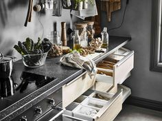 A kitchen worktop with a cutting board and clear glass storage jars and several open drawers with ash fronts Kitchen Mixer Taps, Kitchen Worktop, Glass Storage Jars, Jar Storage, Cosy Kitchen, Kitchen Decor, Ikea Portugal, Black Sink, Kitchen Storage Solutions