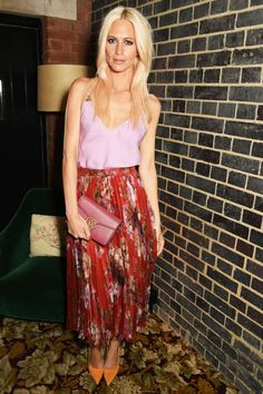 Poppy Delevingne wearing fall's hottest print—a Gucci pleated floral skirt with a pink tank and orange pumps
