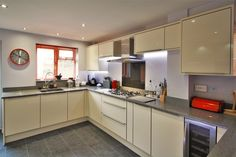 Acrylic gloss kitchen design in Cream with Grey worktops.