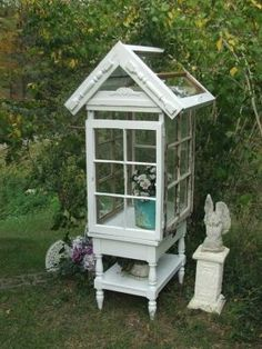 Old window greenhouse on a stand with added architectural detail from a spindle sawed in half and applied to the roof.  How cute! by Peachy Peacherson