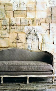 (old pages as wall paper) so much to love here -- that couch, those old papers. grey.