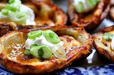 Crispy cheese potato skins, baked to a crisp, then topped with cheddar cheese, bacon, sour cream and green onions.