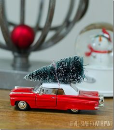 Toy car with bottle brush tree tied to top