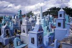 Mexico, Yucatan. Colorful cemetery with statues, paintings, graves, crosses, and family tombs.