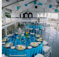 Along with Tina LaMorte of Oh So Fabulous, LLC, Jo-Anne and her team used bright turquoise lamour linens for a laid-back seaside reception on the patio of the Grand Old House in Grand Cayman. To add to the casual vibe, blue and white Chinese lanterns were strung from a tent, and bright yellow orchids added a sunny dose of color to the silver rattan charger plate.    Photo: David Wolfe