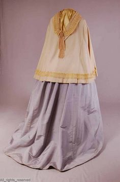1860s short wool and silk burnous. Hood lined with yellow silk satin, body lined with cream satin. Trimmed with wool tassels, silk ribbon and braid. Click through for more and closer views. ModeMuseum Provincie Antwerpen.