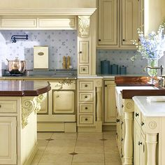 A multitasking European range -- with steamer, griddle, large gas oven, and smaller electric oven -- was ordered in a custom hue to match the cabinets. The appliance is flanked by small drawers that handily store utensils and other cooking supplies.