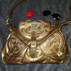 Gold Crossbody/Satchel med-Lrg Perfect for a groovy bike ride, a day at the beach or night on the town.  Great and spacious for anything and everything all around. 2 front snap pkt 100% sales go to a family from fraud. A single mom and her 3 kids were left destitute by her ex husband after he fled indictment by the FBI. No child support/alimony and no warning. Their whole life was a lie and now their left to pick up the pieces through foreclosure and repossession suffering his consequences…