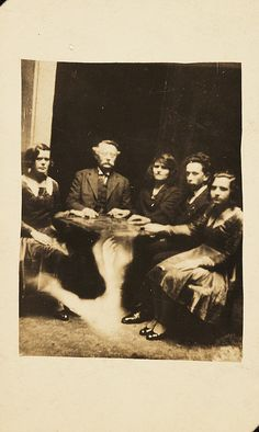 A seance  A photograph of a group gathered at a seance, taken by William Hope  (1863-1933) in about 1920. The information accompanying the spirit  album states that the table is levitating.  In reality, the image of a  ghostly arm has been superimposed over the table using a double  exposure.Collection of National Media Museum