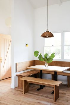 minimal dining room with built-in banquette seating and matte wood floors