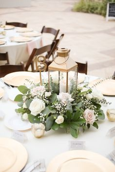 Rustic Nautical Outdoor Wedding Reception Round Table Decor with Gold Hurricane Lantern and Low White Rose with Greenery Centerpiece, Gold Chargers and Tea Candles, Light Blue Tablecloth and Pink Linens, and Brown Wood Folding Chairs