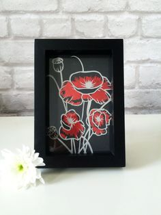 Hand cut wild flower design in grey card mounted over black card with red foil details and presented in a black box frame.  - 175gsm grey card used for the papercut - total frame size is 12.5 x 17.5 x 2.5cm with glass front - includes stand and hooks on the back of the frame to hang - artist initials and year on the mount  This design was inspired by some photographs I took whilst on trip to Milan. There were beautiful wild flowers across the city and countryside including some poppies…