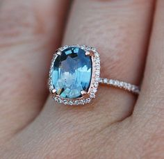 Light Blue Sapphire Engagement Ring in Cushion Cut with Surrounding Diamonds Set in Rose Gold Band