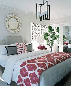 Lovely bedroom done in a simple color scheme of whites, grays, and beiges with touches of red and pink on the floral design coverlet, the red geometric pattern pillow, and vase of beautiful red flowers.  I also love the decorative mirror above the bed, it adds a hint of sparkle.