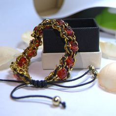 A bracelet made of a chain, glass beads, and cord (1.5MM Black And Soft Cotton Waxy Cord.) A tapestry needle can be used to weave the chord through the chain and beads. The size of the bracelet is adjustable.