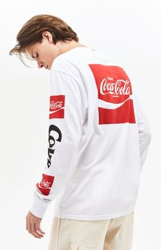 Crack open some refreshing style with help from the PacSun x Coca-Cola Collection. The Coca-Cola Ribbon Long Sleeve T-Shirt has a crew neck and brand graphics on the front, sleeves, and back. Coca Cola Shirt, Pacsun, Graphic Tees, Long Sleeve Tees, Rain Jacket, Shirt Designs, Menswear, Man Shop, Sleeves