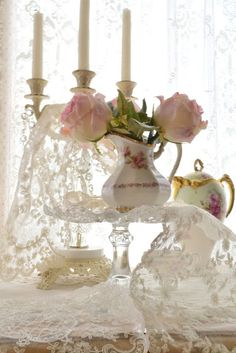 I love the draping of lace with the candelabra and roses in antique pitcher on a glass pedestal, so feminine, delicate, romantic