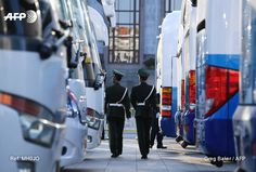 Paramilitary police officers patrol between delegates' buses during the 2nd second plenary session of the National People's Congress in Beijing on March 8, 2017. More than 3000 delegates from across...