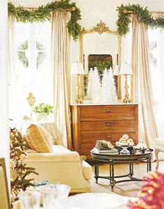 """""""Swags of noble fir crown each window, while vintage-inspired white feather trees nestle on a marble-top chest."""" Houston, Texas, home of Michelle Stewart and family. Interior design by Michelle Stewart. Photographed by Tria Giovan. Written by Jill Kirchner Simpson. """"White Christmas"""" produced by Susanna Showers Moldawer. Southern Accents (November – December 2005)."""