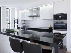 This modern black and white kitchen features Belgian Moon Caesarstone quartz countertops. Stunning interior design for a modern kitchen.
