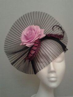 Tocado con crin plisado negro,con adorno de flor y plumas en rosa.