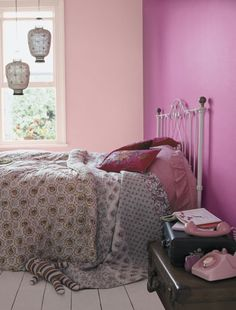 Bohemian pink!  Create a slightly eclectic feel by painting bedroom walls in different pinks. This room is a jumble of colours patterns and together creates a bit of a 'gypsy' look and relies on a mix of strong colour and pattern for effect. Paint colour by Dulux.