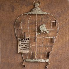 The Birdcage Wall Hanging with Photo Clips is made from lightly distressed metal, which is a common material in cottage style homes, $42.00