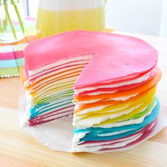 Colorful crepes stacked high to create the happiest cake!