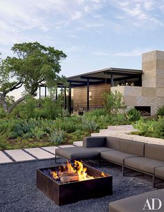 At decorator Sara Story's family compound in Texas, a sleek sectional sofa provides ample seating around the fire pit.