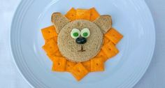 lion sandwich - bread/sandwich face and ears, cheese eyes, blueberry nose, chopped raisin mouth