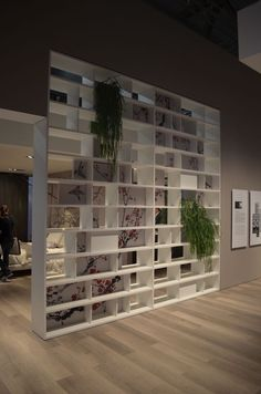 Shelf partition wall. Not this style but like the idea of art and plants being incorporated.