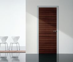 Modern interior swing door featuring a wood slab panel with anodized aluminum stationary jamb and casing