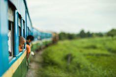 A young Buddhist monk leaning through the open window of the train, Circular Railway, Yangon, Myanmar Photographer: Gavin Gough