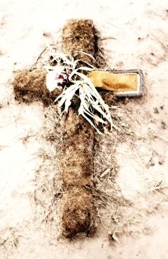 A worn-out cross and withered flowers are the sole decorations on a plot in St. George Cemetery, Kansas