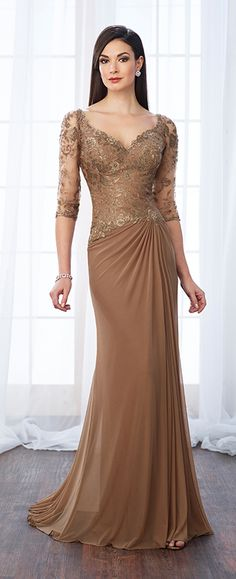 Stretch mesh and lace fit and flare gown with illusion lace three-quarter length sleeves, front and back V-necklines, side gathered skirt, center gathered back skirt with sweep train.