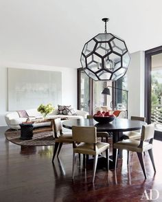 Fashion designer Josie Natori's warm and inviting retreat in Palm Beach, Florida, features a honeycomb-like lantern above a BDDW table and Kerry Joyce for Dessin Fournir chairs in the living and dining area.