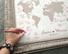 10 Creative Wedding Guest Book Ideas: Wedding Guest Book Map | Ask your guests to sign a map of the world that you can then use to track your travels together. Here & There has a selection of fantastic customized Wedding Guest Book Maps. You could also purchase an inexpensive World Map ($0.89) to use and then have it framed after the wedding.