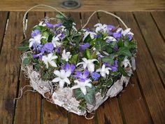 Hart met rand van schors, gevuld met maagdenpalm en witte hyacinth, temidden van divers groenmateriaal