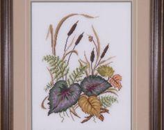 Cruz cosida puple violetas, rosa oscuro y un lirio de tigre naranja están rodeadas por pequeñas flores amarillas en una foto enmarcada. Este cuadro de punto de cruz contado de un diseño de Jean McIntosh fue cosida en 32 Conde lino de Belfast. Para resaltar la labor, el centro era un círculo cortado fuera de las esteras dobles. Profesionalmente se extendía y enmarcado en un marco de lavado de oro pálido.  La foto enmarcada medidas 14(35.5cm) ancho de 14(35.5cm) alta.  Provenga de un ambiente…