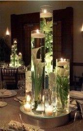 Centerpieces with mirror, water, flowers, & floating candles.  flowers/ oranges