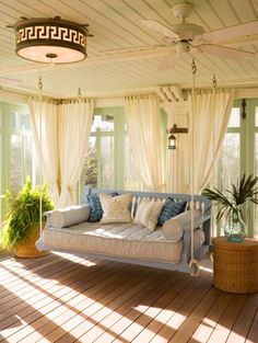 A porch with a swinging daybed