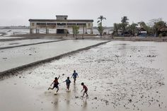 BANGLADESH. Sathkira District. 2010. Children play football in a village devasted by cyclone Aila in 2009. The concrete building in the background is one of over one thousand cyclone shelters erected after 1991.