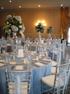 light blue wedding theme- light blue table linens, blue accents in the flower centerpieces, and light blue tulle on silver chairs