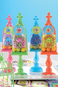 Sweeten up your party decor with a multi-colored arrangement of birdcages filled with candy.