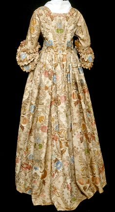 Robe a l'anglaise wedding dress (rear view), ca. 1760s (?), England, brocade (textile)  lace (needlework), lampas, silk (textile). Multi-color floral pattern on cream ground with brown throughout. Ogee motif enclosing central flower and lace-like bands, pleated front neckline, elbow length sleeves with four ruffles. Pleated around waist, bodice lined with linen. Historic New England
