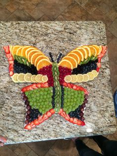 Butterfly Fruit Tray (my version). I drew the butterfly on foam board, cut it out, and covered with foil. Then I spread a light layer of sweet cream cheese on the foil so the fruit would not slide and arranged the fruit--kiwi, strawberries, oranges, lemons, globe grapes (cut in half), green grapes, blueberries, blackberries, raspberries.