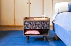 Combinando legno scuro, piedi sottili e un cassetto con motivi geometrici, il comodino Balkis presenta uno stile vintage.