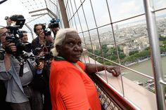 Australian aboriginal artist Lena Nyadbi looks at the photographers as she takes on a view of paris from the Eiffel tower in the inauguration of her giant art work displayed permanently on the roof of Quay Branly Museum.