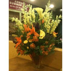 Yellow Snap Dragons, Orange Lily, Yellow Tulips and Orange Alstrameria in an Orange Glass Vase