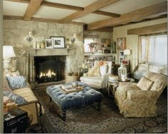 Exposed beams and a stone wall with comfy overstuffed chairs, very charming.